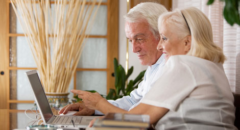 Two older people using a laptop