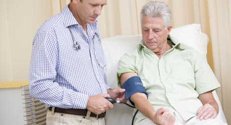Doctor taking blood pressure of an older man